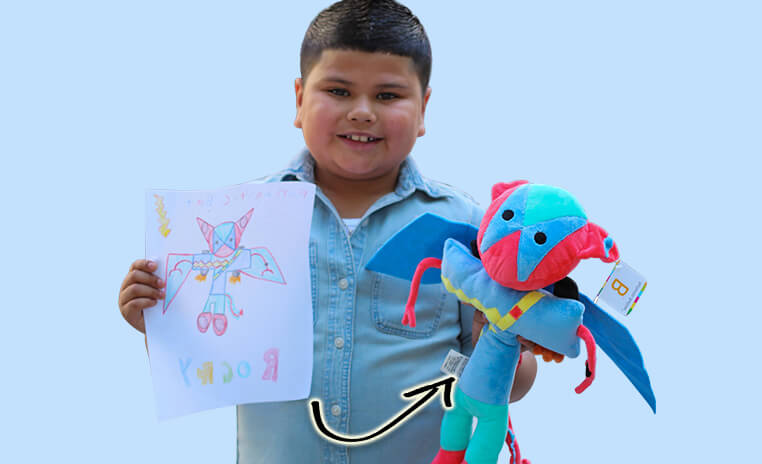 boy holding drawing that was made into stuffed animal